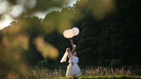 Sensual moment of love. Happy groom carryes in hands beautiful blonde bride with balloons. Sunny summer field background stock video footage