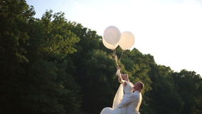 Sensual moment of love. Happy groom carryes in hands bride with balloons. Sunny summer field background stock video