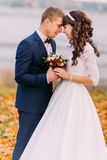 Sensual moment of young newlywed bridal couple on autumn lakeshore full orange leaves Royalty Free Stock Photos