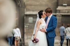 Sensual newlywed couple hugging & kissing near old church.  Royalty Free Stock Photos