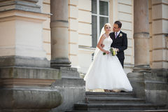 Sensual newlywed couple hugging near old building with columns Stock Photography