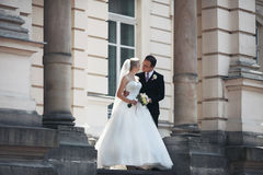 Sensual newlywed couple hugging near old building with columns Stock Photos