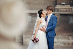 Sensual newlywed couple hugging near old church Stock Images