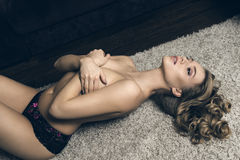Sensual nude woman on carpet Stock Images