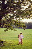 Sensual outdoor portrait of young stylish couple posing in field Stock Photos