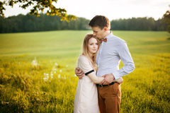 Sensual outdoor portrait of young stylish couple posing in field Royalty Free Stock Photography