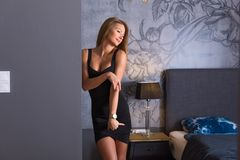 A beautiful woman in an elegant dress standing in a bedroom. Sensual photo of a beautiful woman in an elegant black dress while standing against a wall in a royalty free stock photos