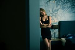 A beautiful woman in an elegant dress standing in a bedroom. Sensual photo of a beautiful woman in an elegant black dress while standing against a wall in a royalty free stock images