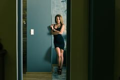 A beautiful woman in an elegant dress standing in a bedroom. Sensual photo of a beautiful woman in an elegant black dress while standing against a wall in a stock images