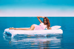 Sensual photo of female lying on bed in sea Stock Image