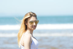 Sensual portrait of beautiful girl with sunglasses on the beach. Portrait of beautiful girl with sunglasses on the beach Royalty Free Stock Images