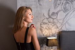 Portrait of a woman in an elegant dress standing in a bedroom. Sensual portrait of a beautiful woman in an elegant black dress while standing against a wall royalty free stock photos