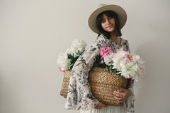Sensual portrait of boho girl holding pink and white peonies in rustic basket. Stylish hipster woman in hat and bohemian floral stock photography