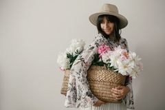 Sensual portrait of boho girl holding pink and white peonies in rustic basket. Stylish hipster woman in hat and bohemian floral stock image