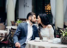 Sensual portrait of the charming beautiful newlywed couple gently rubbing noses while sitting at the restaurant table. Sensual portrait of the charming Stock Photos