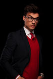 Sensual portrait of classy model in black suit. Wearing glasses posing with hands in pockets while looking at the camera in dark studio background Stock Photos