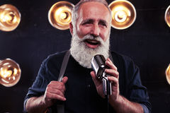 Sensual portrait of personable man in dim light holding a hem of. Close-up shot of personable man singing in a vintage microphone.  over worn background Stock Photography