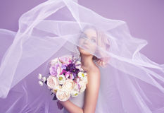 Sensual portrat of young beautiful bride holding flower bouquet. And wearing luxury wedding dress. Flattering veil. Tonned photo Royalty Free Stock Images