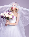 Sensual portrat of young beautiful bride holding flower bouquet. And wearing luxury wedding dress. Flattering veil. Tonned photo Stock Photos