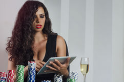 Sensual pretty woman playing poker online via tablet Royalty Free Stock Photography