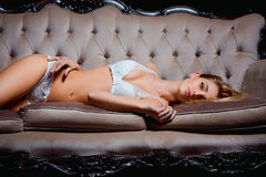Sensual pretty woman in white lingerie on the sofa at luxury interior. Portrait of beautiful attractive and sexy young Royalty Free Stock Photo