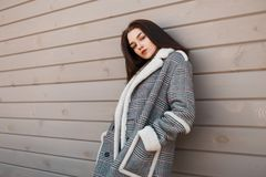 Sensual pretty young brunette woman in a gray luxurious checkered jacket with a white collar is resting standing. Near a vintage wooden building on a warm royalty free stock image