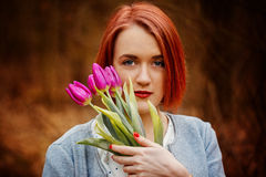 Sensual red girl  with some spring flowers in park Royalty Free Stock Photo