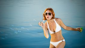 Sensual girl with soap bubbles at the beach. Sensual red girl wearing bikini with soap bubbles at the beach Stock Photos