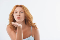 Sensual red-haired lady evincing her feelings. Voluptuous middle-aged woman is sending air kiss to camera. She is standing and looking forward with love Royalty Free Stock Photography