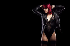 Sensual redhead in body and leather jacket on black Stock Photos