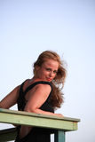 Sensual redhead woman on a wooden railing in the warm summer sunshine with a lovely smile, against blue sky Stock Photo