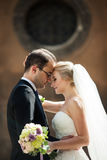 Sensual romantic couple of newlyweds hugging in front of old chu. Rch closeup Stock Photos