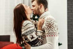 Sensual, romantic couple in warm stylish sweaters with reindeers & snowflakes, handsome man hugging happy woman in front of chris royalty free stock images