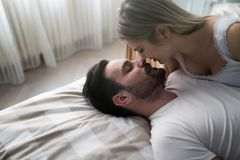 Sensual romantic foreplay by couple in bed. Sensual romantic foreplay by couple in love in bed stock photo