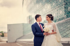 Sensual romantic groom hugging beautiful bride from behind,  on a background of architecture Stock Photography