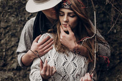 Sensual romantic man in cowboy hat hugging a beautiful gypsy brunette woman from behind, while she is holding a berry tree branch. Sensual romantic men in cowboy royalty free stock photography