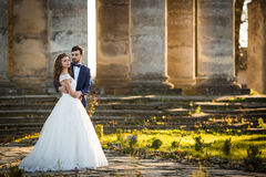 Sensual romantic newlywed bride and groom hugging in front of old baroque church Stock Photos