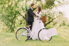 Sensual romantic young newlywed couple posing in park with bicycle Royalty Free Stock Photos