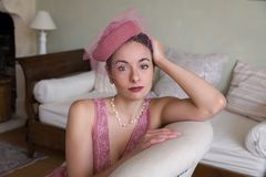 Woman in 1920s dress on settee. Sensual 1920s woman in pink flapper dress sitting on an antique chaisee longue or recliner royalty free stock image