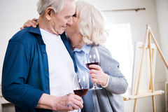Sensual senior couple drinking wine in art workshop. Side view of sensual senior couple drinking wine in art workshop Stock Images