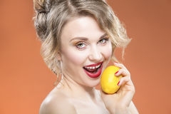 Sensual Sexy Caucasian Blond Girl Biting Yellow Lemon Fruit. Posing Against Orange Background. Royalty Free Stock Images