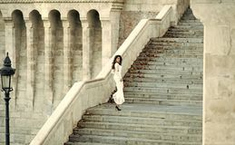 Sensual sexy woman. Fashion bride in white wedding dress on staircase. Fashion model with long hair on stair steps Stock Photos