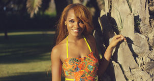 Sensual sexy young African woman. Standing in a colorful swimsuit holding the trunk of a tropical palm tree and smiling at the camera Stock Photography