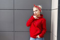 Sensual sexy young blonde woman in a vintage bandana in a red stylish sweatshirt in blue jeans posing outdoors near a gray wall. On a summer day. American royalty free stock photography