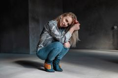 Sensual sexy young blonde woman in vintage cowboy boots in summer shirt in fashionable ripped jeans sit in a room with sunlight. American beautiful fashion royalty free stock images