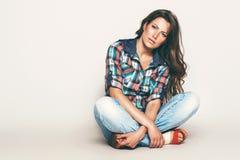 Sensual sitting woman in check shirt Stock Image