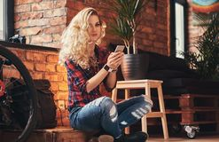 Sensual blonde hipster girl with long curly hair dressed in a fleece shirt and jeans holds a smartphone sitting on a. Sensual smiling blonde hipster girl with Stock Images
