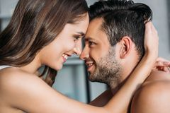 Sensual smiling couple touching with foreheads and looking at each other. At home royalty free stock photography