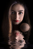 Sensual smiling woman. In water with reflection on black background Royalty Free Stock Images