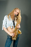 Sensual smiling yong blonde with saxophone Stock Photos